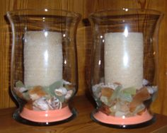 "Matching hurricane beach candle set.   Candles have a grainy sand finish; burned once.  Coral sand in the bottom, with lots of great beach glass accents.  Aprx. 10-12"" high.    $20/pair."