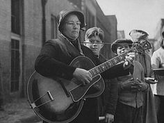 In April 1939, a woman soldier in the Salvation Army played a guitar solo for street urchins in a San Francisco slum. The Great Depression was grinding along, year after year, as government projects failed to create prosperity. The photograph was made by the celebrated Dorothea Lange, for the Farm Services Administration.