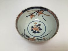 Bowl with iris and peony flowers in the interior and chrysanthemum and roundels with landscape on the exterior. Made of porcelain with underglaze cobalt blue and overglaze polychrome enamels.