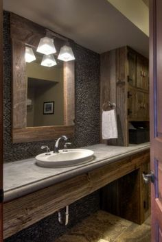 Pebble wall in bathroom with rustic cabinets