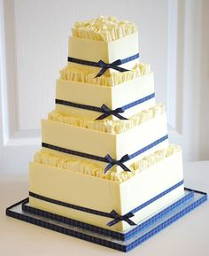 Scottish themed chocolate box. This is a cake with white chocolate wrapped around. It also has white chocolate tight ruffles and tartan ribbon on the board and all 4 tiers.