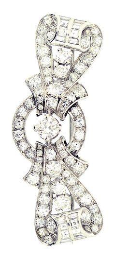 An Art Deco platinum and diamond brooch, circa 1935. Comprising of central brilliant-cut diamond with interlocking links of circular and baton diamonds. #ArtDeco #brooch