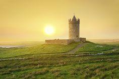 Está é uma vista típica da Irlanda. construções de pedra e muito verde. Na foto vemos o Castelo Doonagore ao pôr-do-sol. Trata-se de uma casa torre do século 16 rodeada de um pequeno recinto amuralhado localizado a cerca de 1 km acima da vila costeira de Doolin no Condado de Clare. Quem gosta de histórias e cenários medievais TEM que visitar o país! Conhece? Escreva uma dica para nós!  #ViNoCatraca #ViagemLivre : Patryk Kosminder-iStock