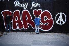 """Deux hommes peignent un tag """"Pray for Paris"""" (Priez pour Paris) en hommage aux victimes des attaques à Paris le 14 novembre 2015Deux hommes peign..."""