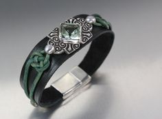 I bezel set the stone in fine silver and then hand cut, dyed and finished the leather. It looks black in the picture but it is really dark green. --Lisa Barth