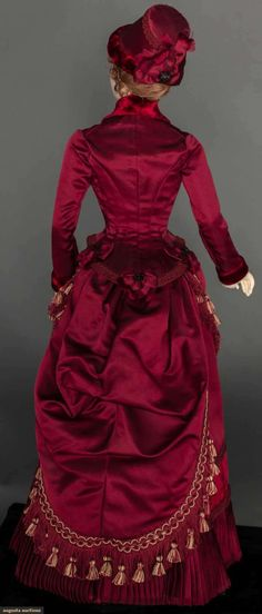 "29"" figure, period accurate 1885 visiting dress created & hand sewn by fashion designer John Burbidge: deep red silk satin & velvet bustle skirt & jacket, lace blouse, fringed & tasseled over skirt, includes matching parasol & hat, shoes, undergarments, all excellent. This is one of 75 ""ladies"" each costumed in a 1860 through 1914 unique ensemble, as seen in the book ""Les Petites Dames de Mode"" & numerous museum presentations throughout the U.S."