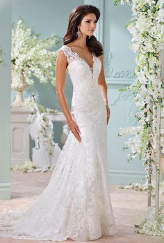 Brides: David Tutera for Mon Cheri. Hand-beaded Alençon lace appliqués and tulle over charmeuse slim A-line cage dress with slight cap sleeves. Plunging scalloped V-neckline with illusion modesty piece. Lace appliqué illusion back bodice with crystal button closures. Satin slim underskirt with sweep train. Tulle and lace appliquéd cage overskirt with scalloped hem and chapel length train.