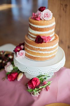 "A pretty ""naked"" cake accessorized with roses."
