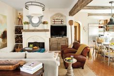 Use architectural details, like the cedar ceiling beams in this room, to help visually divide and define the rooms in the open space of a great room.  See this Internationally Influenced Great Room