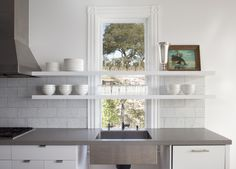 Floating kitchen shelves and sink of Belvedere renovation by Mark Reilly Architecture | Remodelista