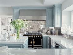 Pale blue cabinets, glossy thick countertops, a La Cornue range, and lots of sunlight.   Interior Designer: Michelle Workman. Home of Jennifer Lopez.