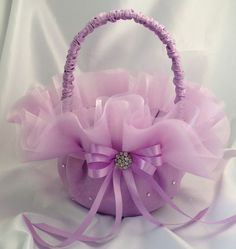 Gorgeous custom flower girl basket with layers of lilac organza accented with Swarovski rhinestones and a tied with a lilac satin bow and rhinestone button