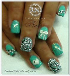 mint green acrylic nails with bows and gems.