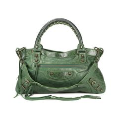 The Balenciaga Motorcycle bag is a classic 'It' bag that has been a favourite of celebrities and stylish women alike. The First style of this bag in a forest green distressed lambskin features hand stitched handles and a removable shoulder strap. The top zip closure is designed with a leather tassel zipper pull. The hardware of this bag is in aged brass. The bag also comes with a leather framed hand mirror for convenient touch ups. Please note that there are signs of wear on the tassels…