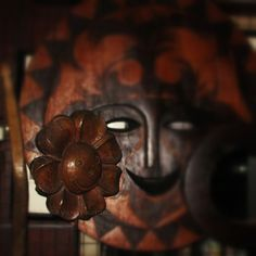 solid wood sculpture of a flower with a smiling face