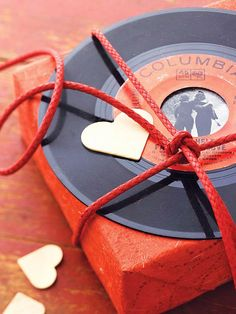 "GREAT IDEA! Browse thrift shops for 45s with special significance, such as Elvis singing ""Can't Help Falling in Love,"" to decorate a box of chocolates. Attach a personal photo to the back of the record with artist's tape before tying the vinyl in place."