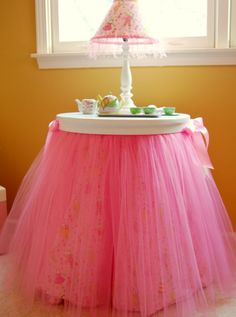 Well, this has been a long obsession, and here it is: the TUTU Table Topper. Custom made for you by a professional woodcrafter here in the USA! Our topper makes your small round 3 legged table look SO FLUFFY and just like a BIG Ballerina Skirt! It is Gorgeous!! The topper is painted white and featuers 2 satin bows on each side of the topper. The tulle is attached and hangs down. Topper is 3\/4 inch thick birch. You can order your topper in these colors: Paris Pink is shown Lavender...