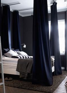 The dark blue painted walls of this bedroom along with the crisp white sheets on the bed help create a feeling of calm. Dark blue padded curtains around the bed block out sounds and light. A dark brown rug on the wooden floor adds softness and warmth.