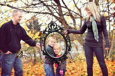 Cute idea for family photo! Large rectangle frame around the kids - older two holding it- mom and dad hugging in back corner