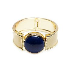"""Lourdes Gold Lapis  Mined as early as 7000 BC, lapis lazuli has been prized for its uniquely vivid blue color, on full display hear against a matte gold band. Lourdes features a one inch circular lapis stone, for a classic look that will elevate the most casual of outfits, and pair perfectly with evening attire.   - Gold tone metal, lapis - 2 2/5"""" in diameter, 1"""" wide - Magnetic hinge closure"""
