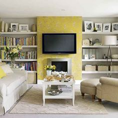 like the shelves to the sides of the tv & a pretty yellow wallpaper accent wall
