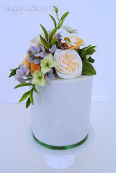 Sugar flower cake, Birthday cake, double barrel cake with sugar flowers in lavender, yellow and green shades. Sugar roses, hydrangeas, daisies, buds and leaves.