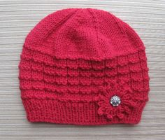 """This hat is knitted in the round on circular needles and does not have a seam. The pattern includes instructions for the knitted flower.The hat can be made in any medium worsted/aran (10ply) yarn with gauge of 4.5 sts per 1""""."""