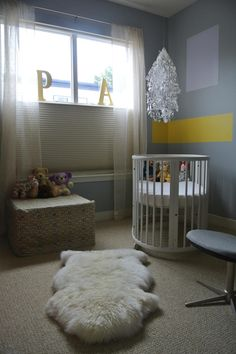 StudioHue chose to apply a neutral background color--gray--to this little girl's nursery so that the room could be easily changed as she grows. The designers added highlight colors, shapes and fabrics to add interest, such as the white scalloped mobile over an oval crib, geometric shapes painted on the wall and a soft fur area rug atop the carpet.