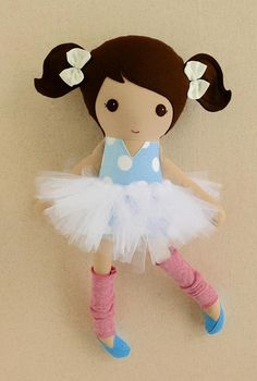 This is a handmade cloth doll measuring 20 inches. She is wearing a sweet, blue and white polka dotted, v-neck top with a removable, white, tulle tutu, pink, knit leg warmers, and baby blue shoes. Her brown hair is worn in high ponytails and accented with white, fabric bows. She is made from 100% cotton fabrics, wool blend felt, tulle, and polyester fiberfill. Her seams are triple stitched and she is firmly stuffed with Polyfil. Please hand wash or machine wash on gentle cycle. Lay flat to…