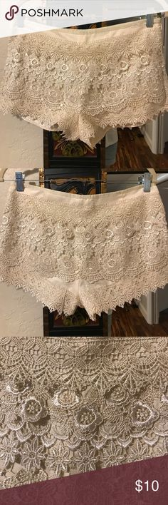 """Lace shorts by Sans Souci Cream colored shorts with lace overlay. Size marked medium but measures smaller through hips. One small part of lace missing (pictured). Waist: 32"""". Hips: 36"""". Waist to hem: 10"""". Sans Souci Shorts"""
