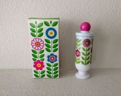 Vintage lotion in a cup by Avon, 1971. In the original box. Bottle is 6 1/2 x 3.  Dutch Treat Demi-Cup Hawaiian Ginger Cream Lotion. Reusable painted milk glass cup filled with fragranced lotion and topped with a metal cap.  The cup is white glass with a mod pink, purple, and green floral motif. The cap is white painted metal with a pink plastic knob. The box is printed with a multicolor mod floral pattern.   Very good vintage condition. This was a sales model for an Avon representative,...