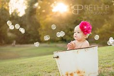 Outside with cake, bubbles, pompoms and a burlap sign