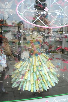 a dress made from paper and mini drink umbrellas. go to the link to see additional views. very cute as a display.