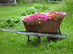 Large old metal wheel barrow with deep tub and cracked handles.