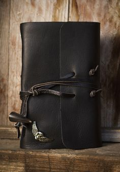 Write in biker style! Smooth, jet black leather accented with silver pyramids and iron-cross rivets on the spine. Doubled Leather strap-and-horn closure holds your book secure!