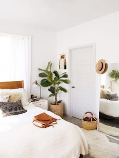 A white bedroom with a wood headboard, a large plant, and rattan baskets.
