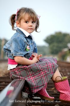 child photography 3 year old girl train tracks jean jacket pink rain boots plaid skirt cupcake pin cute pose