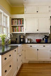 Cream cabinrts, dark counters, gray backsplash, pale yellow paint, farmhouse sink