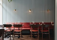Finnish designer Joanna Laajisto combined mint-coloured corrugated metal wall panels with red-orange marble furniture, inside this restaurant in Helsinki