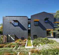 Diamond scalloped and brick-shaped shingles cover Melbourne house by Austin Maynard Architects