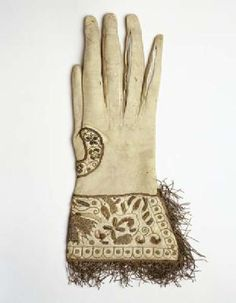 Kid leather glove C.1610-1650.  @ Museum of London.    white kid leather glove of unusual design.  Embroidered cuff done separate.