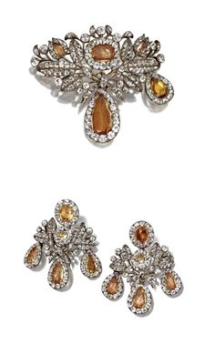 ANTIQUE TOPAZ AND PASTE DEMI-PARURE, 18TH CENTURY. Comprising a brooch and a pair of girandole earrings, set with cushion-shaped and pear-shaped topazes and cushion-shaped pastes in closed-back mountings of silver, drops on brooch and earclips are detachable, one drop missing on brooch, earrings with later-added screw-back fittings. With fitted gilt-embossed leather case.
