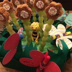 Gezonde traktatie kinderdagverblijf: bloemen van witte druiven met ontbijtkoek en vlinders met een stempelstift erin (Action). Met de Maya de Bij caketopper van fondant er gezellig tussen in!