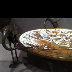 Three birds hold a beautiful dish aloft. I love the feather detailing on the birds, not to mention the dish itself.