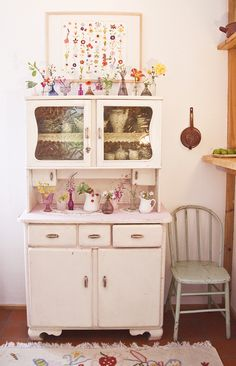 Wow...very pretty vintage white cupboard with lots of pretty flowers and vases on display...