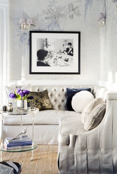 A simple, elegant and classic living room features a black and white photo of Audrey Hepburn above the tufted L-shaped corner sofa  (via Simple Dwellings)