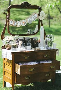 A tea bar with a hanging banner and assorted jars of teas on an antique dresser | Brides.com