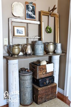 Love this display short columns with board on top makes a console table, old window, picture frame, pictures, crates, ironstone and galvanized.