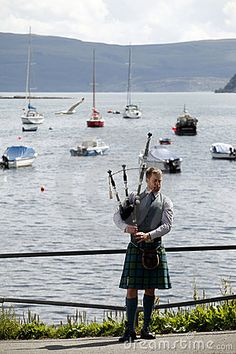 A scottish bagpiper dressed in traditional kilt is singing next to Loch Alsh, in Kyle of Lochalsh village, Scotland, UK