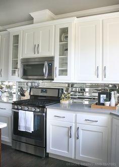 White cabinets, mirror backsplash, dark floors and gray countertops